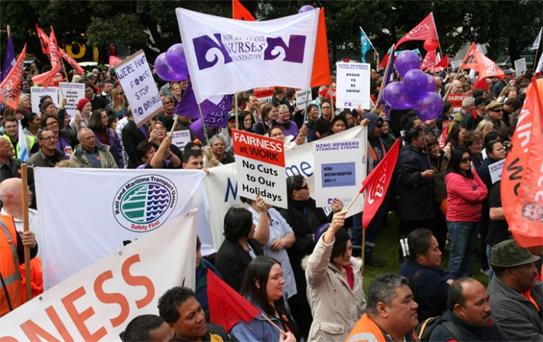 Photograph of union members at a protest holding signs